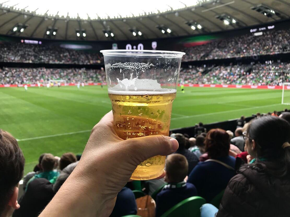 Hand mit einem Plastikbecher mit Bier, dahinter Zuschauer im Fußballstadion