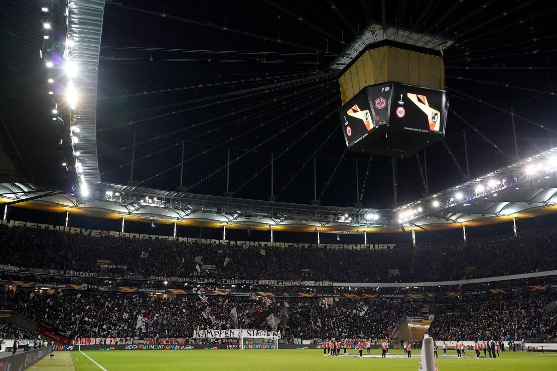 Voll besetztes Stadion mit Videowürfel und Flutlicht