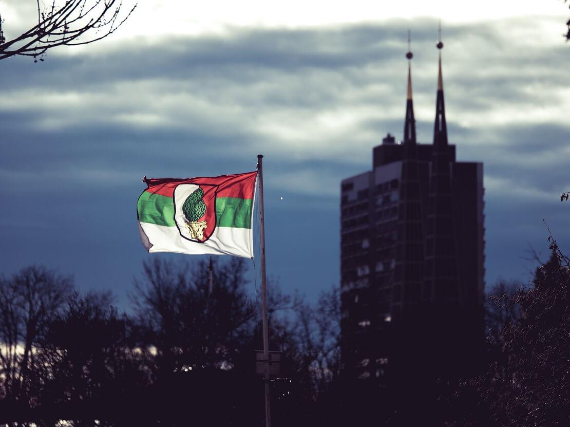 Flagge des FC Augsburg vor einem bewölkten Himmel und der Skyline