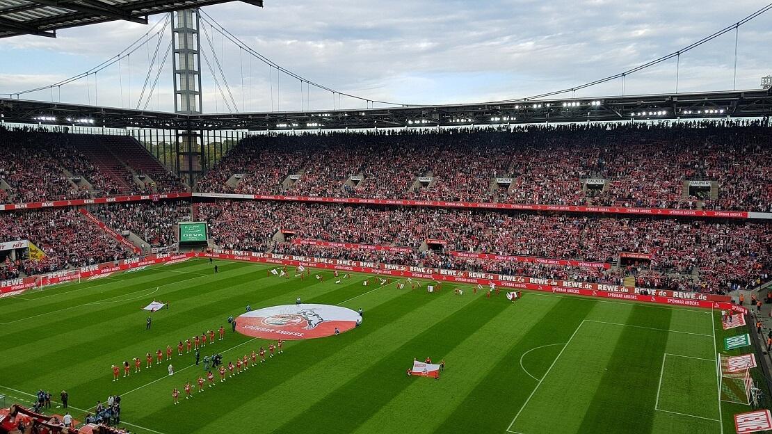 Voll besetztes Stadion des FC Köln mit Wappen in der Mitte