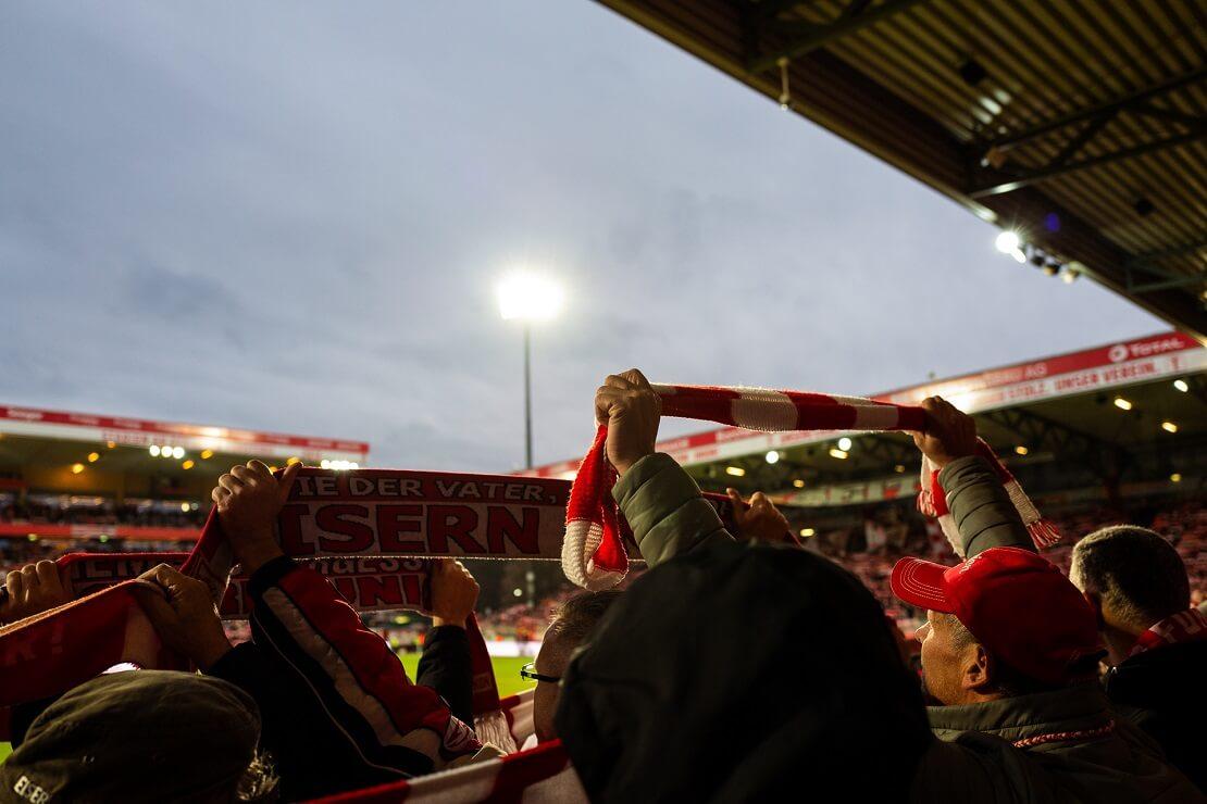 Fans stehen im Stadion und halten fanschals der Union Berlin hoch