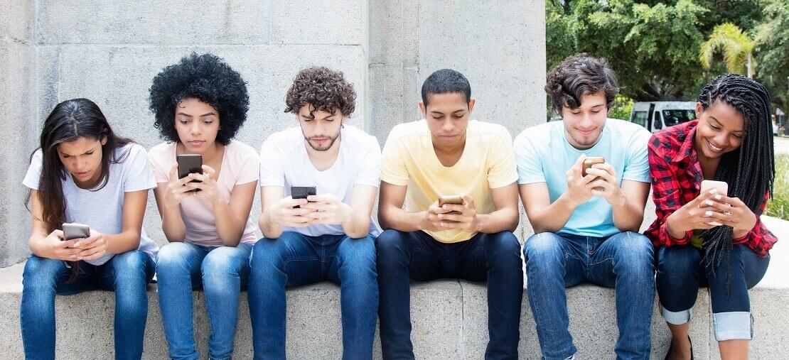 Gruppe Jugendlicher sitzt in einer Reihe an ihren Handys