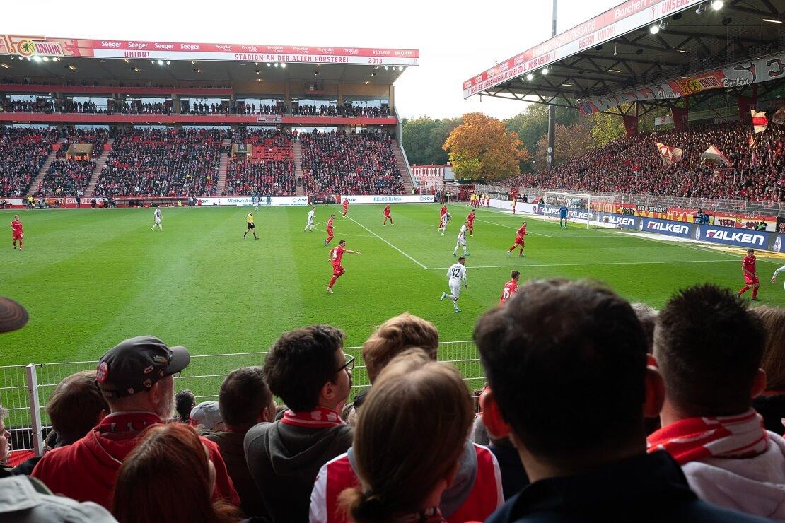 Union Berlin spielt in einem Stadion im Vordergrund sitzen Fans
