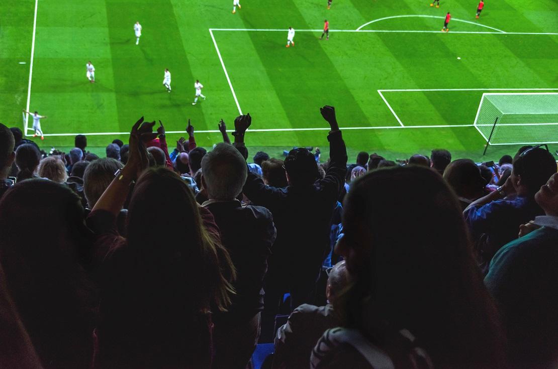 Fankurve bejubelt ein Tor, unten steht Spieler an der Eckfahne