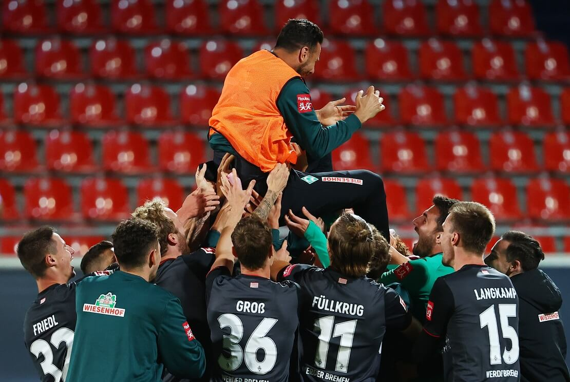 Spieler von Werder Bremen werfen Claudio Pizarro in die Luft