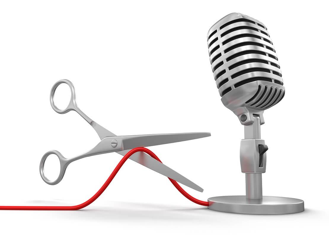 Eine Schere schneidet Kabel zu einem Mikrofon durch