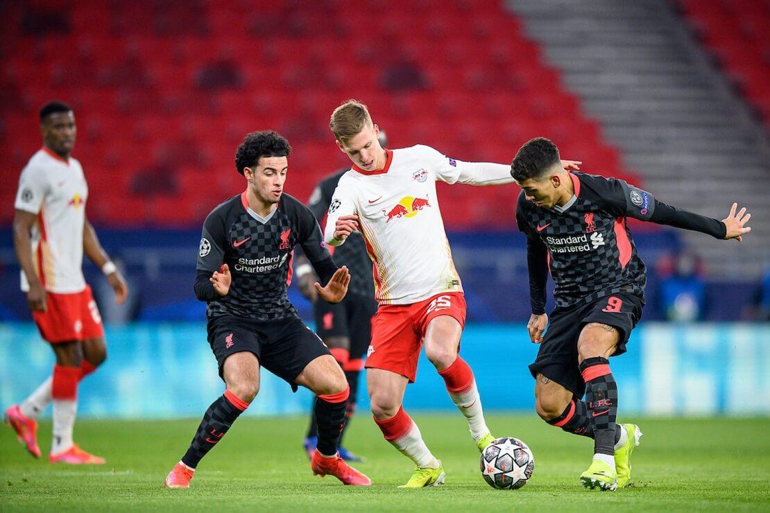 Dani Olmo von RB Leipzig dribbelt gegen zwei Spieler des FC Liverpool