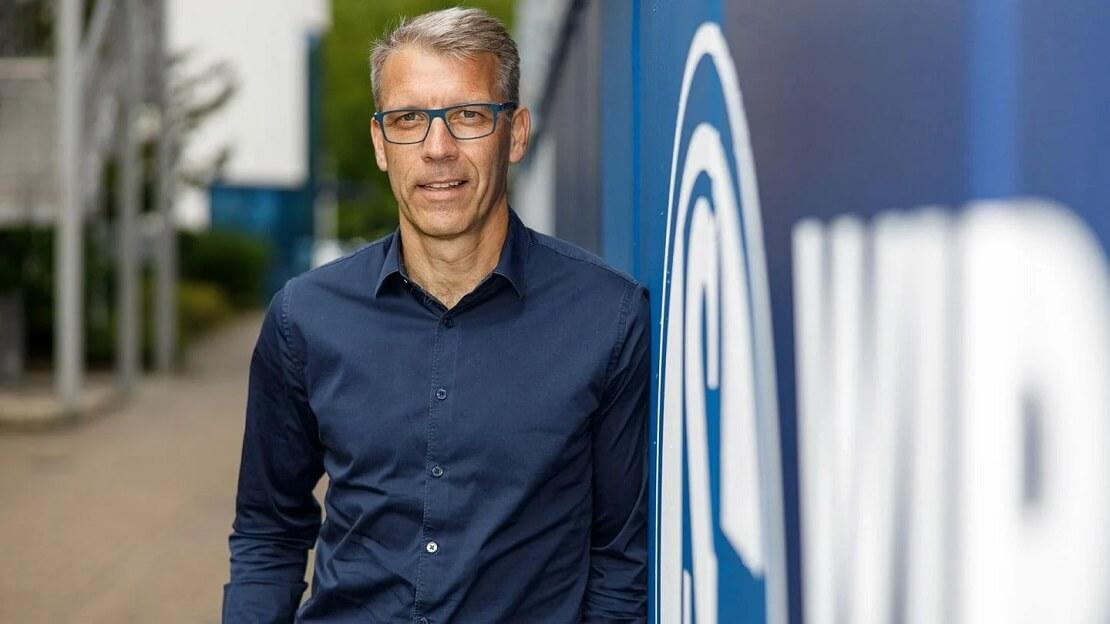 Peter Knäbel neben dem Wappen von Schalke 04