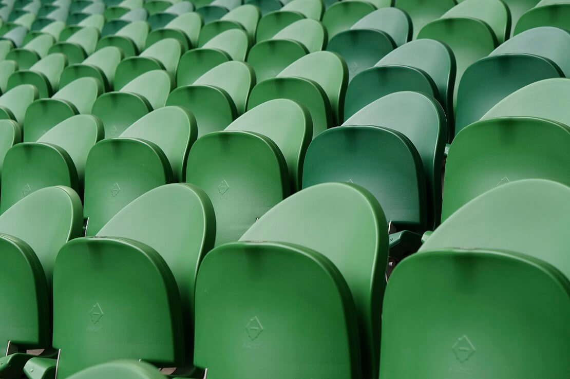 Leere, hochgeklappte grüne Sitze in einem Stadion
