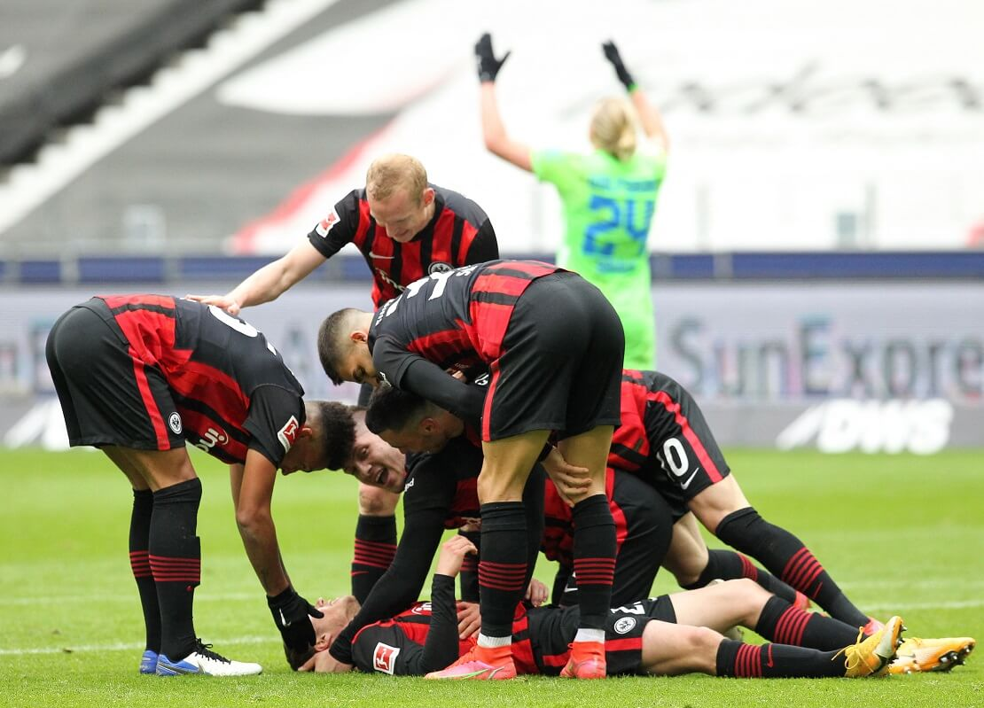 Spieler von Eintracht Frankfurt jubeln auf dem Boden liegend. Im Hintergrund flucht ein Wolfsburger Spieler.
