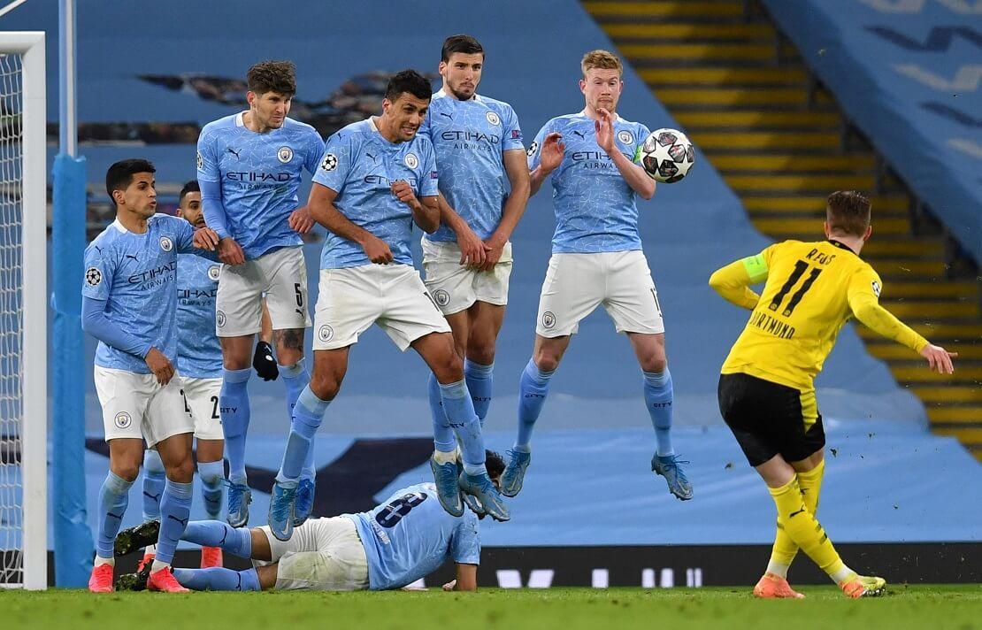 Marco Reus schießt einen Freistoß, Spieler von Manchester City springen in einer Mauer hoch