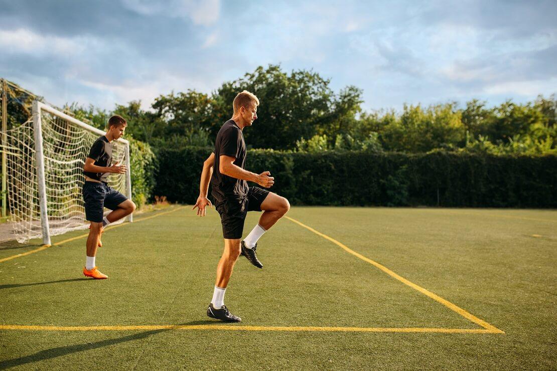 Zwei Männer trainieren auf einem Fußballplatz