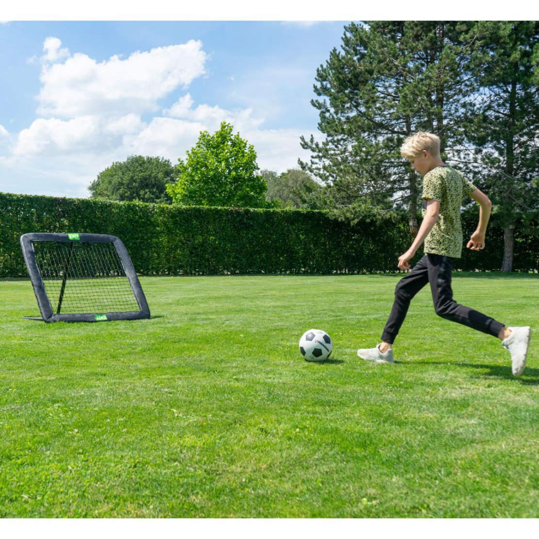 Ein Junge schießt einen Fußball auf einen Fußball Rebounder